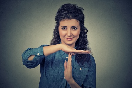 out of control: Closeup portrait, young, happy, smiling woman showing time out gesture with hands isolated on gray wall background. Positive human emotion facial expressions, feeling body language reaction, attitude
