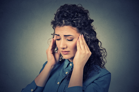 ocd: Closeup sad young woman with worried stressed face expression having headache isolated on gray wall background. Human emotions, mental health concept Stock Photo