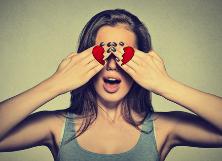 truelove: Beautiful young woman eyes covered by hands with broken heart printed on them. Girl in love isolated on gray wall background Stock Photo