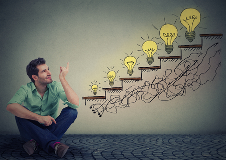 career success: Happy man sitting on floor in his office pointing at business education success, promotion, company growth isolated gray wall texture background. Handsome guy looking up at growing up light bulbs Stock Photo