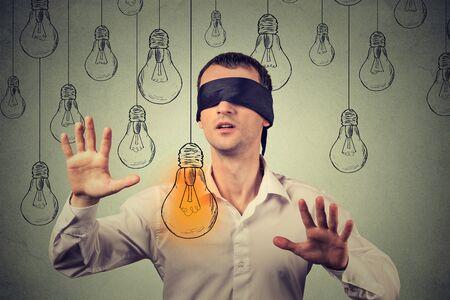 ojos vendados: hombre joven con los ojos vendados caminando a trav�s de las bombillas en busca de brillante idea
