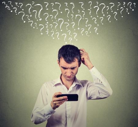 Retrato de hombre joven confundido mirando su teléfono móvil inteligente tiene muchas preguntas aisladas en el fondo de la pared gris. expresión de la cara humana Foto de archivo