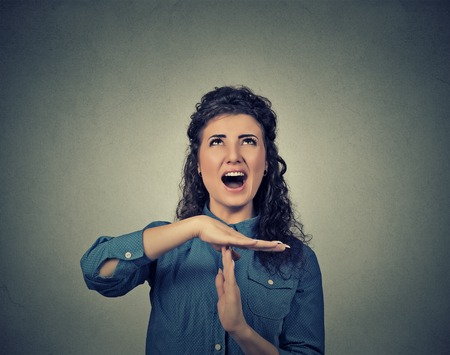 out time: Young woman showing time out hand gesture, frustrated screaming to stop isolated on grey wall background. Too many things to do. Human emotions face expression feelings reaction Stock Photo