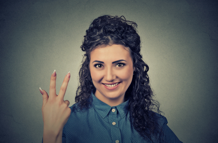 trilogy: Closeup portrait of young pretty woman giving a three fingers sign gesture with hand isolated on gray wall background. Positive human emotions, facial expressions, feeling, symbols, body language