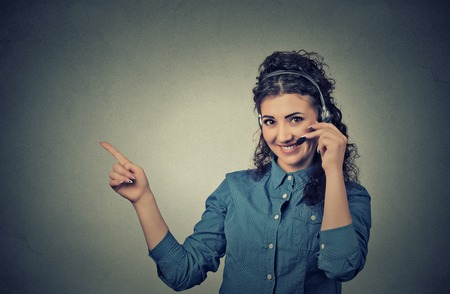 telephonist: Closeup portrait of beautiful, adorable smiling female customer representative with phone headset pointing at copy space isolated on gray wall background. Positive human emotions, facial expressions