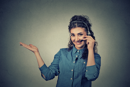 presenting: Closeup portrait of beautiful, adorable smiling female customer representative with phone headset pointing at copy space isolated on gray wall background. Positive human emotions, facial expressions
