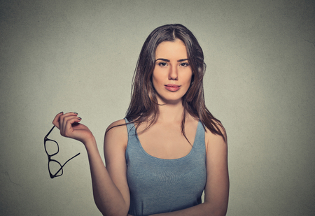 correction: Closeup attractive woman holding pair of glasses she doesnt need anymore, surgical correction of eyesight concept Stock Photo