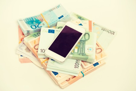 budget repair: Smart phone with money concept. Euro banknotes. Online new technology job reward income. New gadget expenses. Data plan price Stock Photo