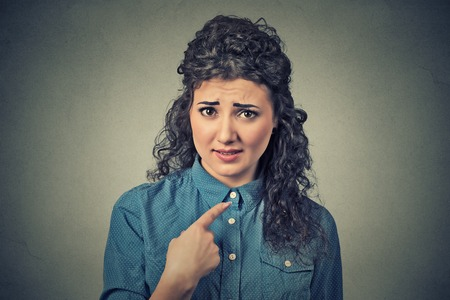 Retrato de mujer loca enojado, triste, molesto joven, consiguiendo loco pregunta que le solicitará que hablar conmigo, te refieres a mí? Aislado en el fondo de la pared gris. Las emociones negativas, las expresiones faciales Foto de archivo