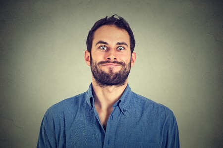 crazy guy: Crazy looking man making funny faces isolated on gray wall background