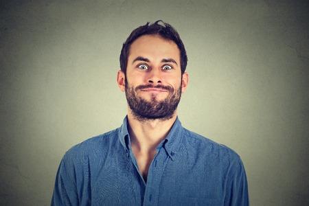 gente loca: Hombre loco que mira haciendo gestos aislados sobre fondo gris de la pared Foto de archivo