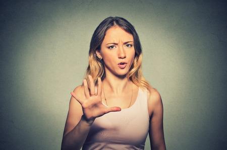 Retrato de mujer molesta enojado que levanta la mano hasta decir no a la derecha allí aislado sobre fondo gris. Foto de archivo