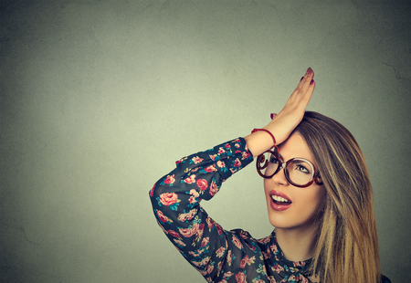 Bedauert, falsch zu machen. Nahaufnahmeportrait dumme junge Frau, Hand auf den Kopf mit duh Moment auf grauem Hintergrund schlagend.