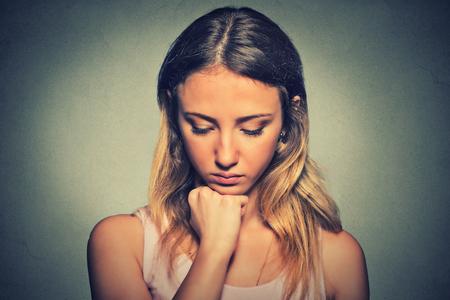 fille triste: problèmes. femme Sad isolé sur gris fond mur