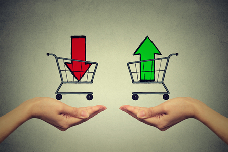 acquirement: Two hands with consumer baskets with up and down arrow signs isolated on gray wall background Stock Photo