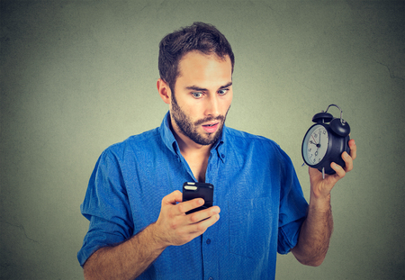 insulted: Portrait perplexed business man with alarm clock looking at smart phone with confused face expression isolated on gray background