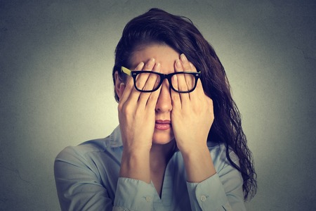 see: Closeup portrait young woman in glasses covering face eyes using her both hands isolated on gray wall background