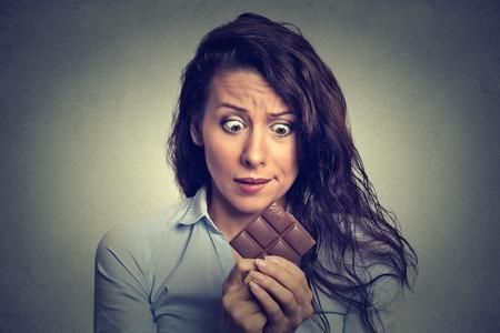 aliments droles: Portrait triste jeune femme fatiguée des restrictions alimentaires craving bonbons chocolat isolé sur gris fond mur. Banque d'images
