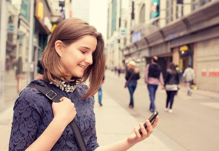 phone message: Portrait happy girl walking and texting on the smart phone in the street wearing a dress in autumn. Stock Photo