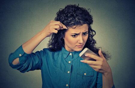 receding hairline: Closeup unhappy frustrated upset young woman surprised she is losing hair, receding hairline. Stock Photo