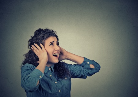 deafening: Closeup portrait young unhappy stressed woman covering her ears looking up stop making loud noise its giving me headache isolated on gray wall background. Stock Photo