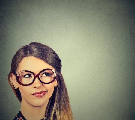 skeptic: Closeup funny confused skeptical woman in glasses thinking planning looking up isolated on gray wall background copy space above head. Stock Photo