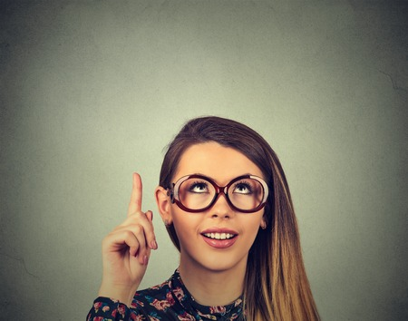 aha: Business woman in glasses pointing with finger up has an idea smiling isolated on gray wall background