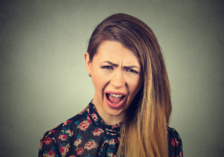 complaining: Closeup portrait angry young woman having nervous breakdown, screaming crying isolated on gray wall background. Negative human emotion facial expression feeling attitude reaction Stock Photo