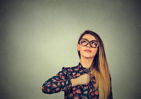 actitud: Muchacha del super héroe. Mujer joven confidente en los vidrios aislados en el fondo gris de la pared. Las emociones humanas se enfrentan a la expresión de la actitud lenguaje de la percepción del cuerpo