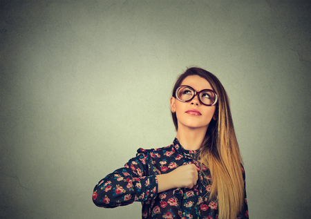 powerful: Superhero girl. Confident young woman in glasses isolated on gray wall background. Human emotions face expression body language perception attitude