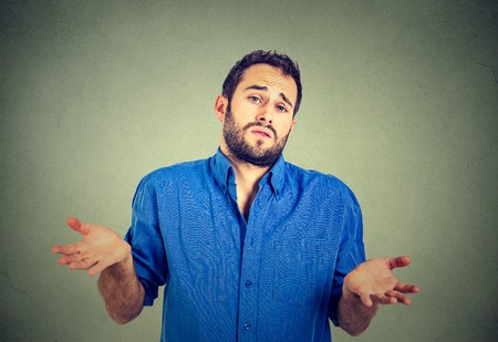 i dont know: Ignorance and arrogance. Closeup portrait young man shrugging shoulders who cares so what I dont know gesture isolated on gray wall background. Human body language. Whatever attitude reaction