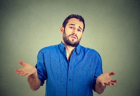 Ignoranz und Arroganz. Nahaufnahmeportrait junge Mann zuckt die Schultern, die kümmert sich so, was ich weiß Geste nicht auf grauen Wand Hintergrund. Menschliche Körpersprache. Was auch immer Haltung Reaktion