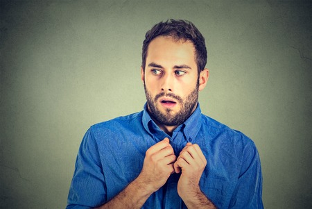 Closeup portrait nervous stressed young man student feels awkward looking away sideway anxiously craving something isolated gray wall background. Human emotion face expression feeling body language