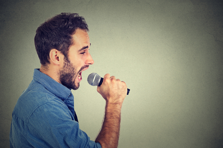 talk show: Singing man isolated on gray wall background