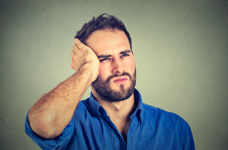 distraught: portrait stressed sad handsome young man looking up thinking isolated on gray wall background. Human face expressions emotions. Unhappy guy with memory loss