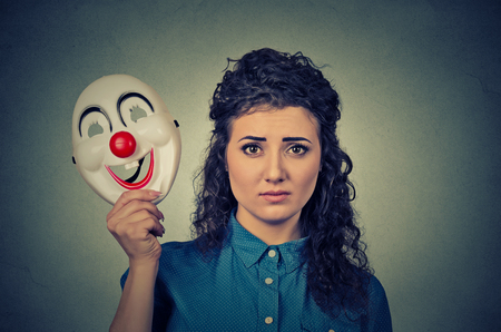 fake smile: Portrait young upset worried woman with sad expression holding a clown mask expressing cheerfulness happiness isolated on gray wall background
