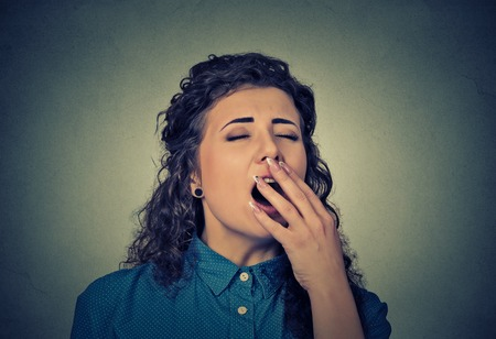 sleepiness: It is too early for meeting. Closeup portrait sleepy young woman with wide open mouth yawning eyes closed looking bored isolated on gray wall background. Face expression emotion body language Stock Photo