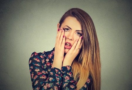 socially: Closeup portrait of frustrated stressed woman with hands on face upset about to cry isolated on gray wall background. Negative human emotion facial expression feelings, body language reaction Stock Photo