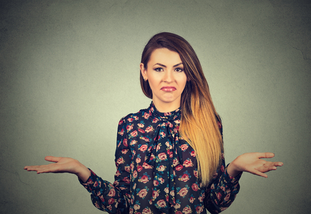 no body language: Who cares so what I dont know. Portrait of a pretty young woman shrugging shoulders isolated on gray wall background Stock Photo