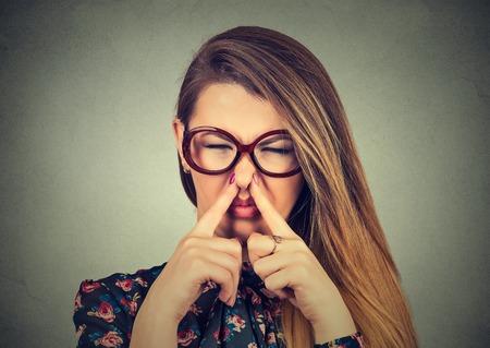 olfato: Primer Headshot de la mujer del retrato pellizca la nariz con los dedos de las manos se ve con algo disgusto apesta situación olor mal aisladas sobre fondo gris de la pared. Expresión de la cara humana de reacción lenguaje corporal