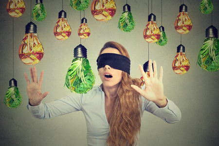 processed: Blindfolded young woman walking through light bulbs shaped as junk food and green vegetables isolated on gray wall background. Diet choice right nutrition healthy lifestyle idea concept Stock Photo
