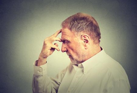 Closeup portret starszego mężczyzny przemyślany samodzielnie na szarym tle ściany