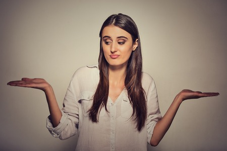 shrugs: Portrait perplexed looking woman arms out shrugs shoulders I dont know cant make a choice isolated gray background. Human emotion, facial expression body language life perception whatever attitude