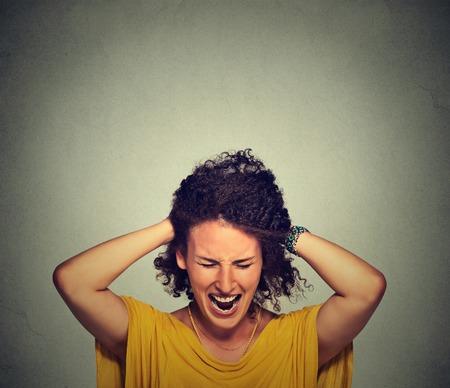 Stress. Frau betont wird crazy ziehen ihr Haar in Frustration auf grauen Wand Hintergrund ziehen. Negative menschliche Emotionen Gefühle Reaktion