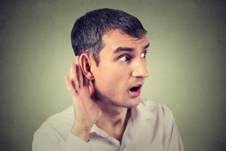 cochlear: Closeup portrait hard of hearing man placing hand on ear asking someone to speak up or listening carefully to a gossip isolated on gray wall background. Human emotion facial expression