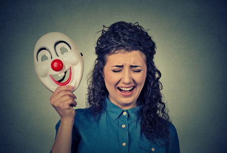 formalities: Portrait young upset crying screaming woman holding a clown mask expressing cheerfulness happiness isolated on gray wall background. Human emotions