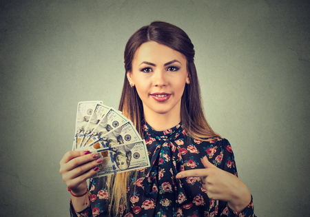 woman holding money: Closeup portrait happy excited successful young business woman holding money dollar bills in hand isolated gray wall background. Positive emotion facial expression feeling. Financial reward concept