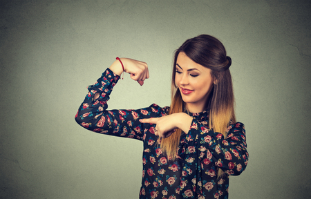 facial muscles: Closeup portrait beautiful fit young healthy model woman flexing muscles showing her strength isolated on gray wall background. Positive emotion facial expression feeling attitude perception wellbeing
