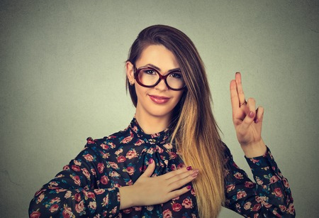 honest: Young woman in glasses making a promise isolated on gray wall background