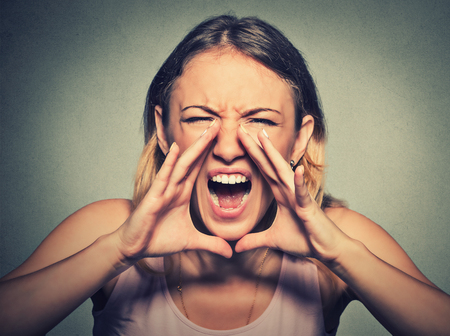 aggravated: Closeup portrait angry young woman having nervous atomic breakdown, screaming isolated on gray wall background. Negative human emotion facial expression feeling attitude reaction Stock Photo